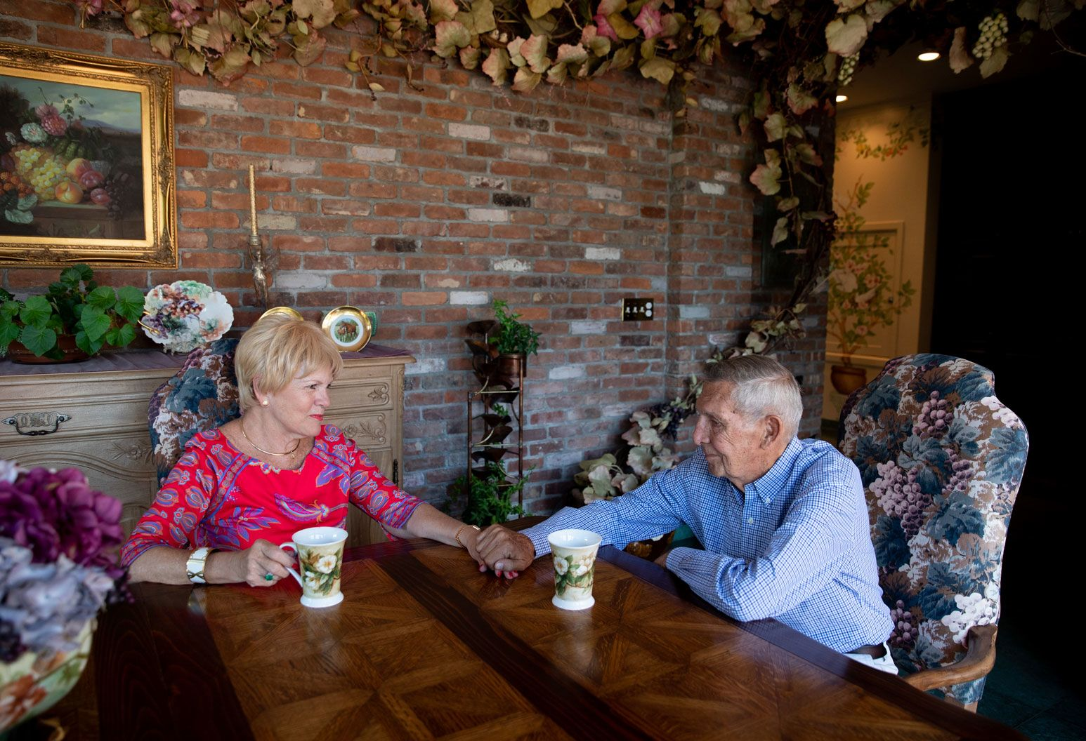 An elderly couple sits at a dining table holding hands. They are in a room with a brick wall, a fireplace, and a lot of floral decor.