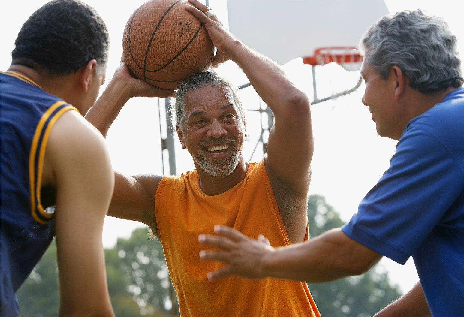 Man in orange sleeveless shirt holds a basketball over his head as two older men wearing blue tops stand in front guarding him from passing.