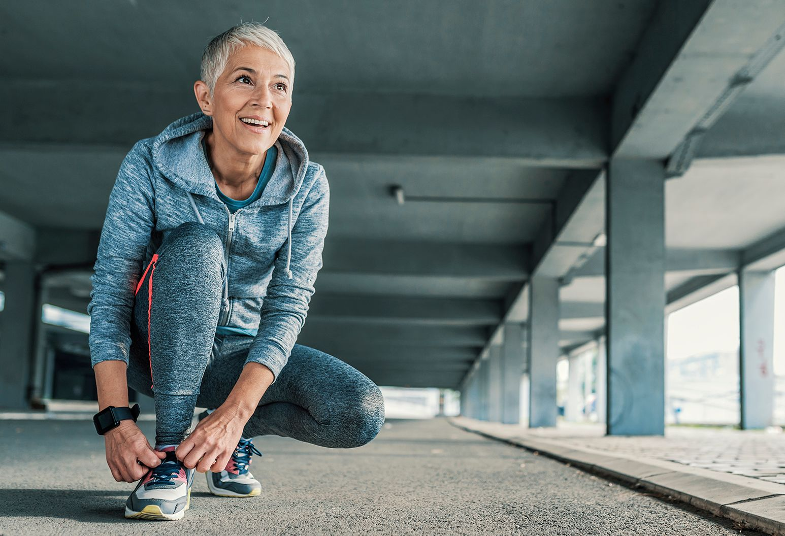 An elderly woman with short gray hair wearing gray work out clothes ties her shoes and smiles before a run.