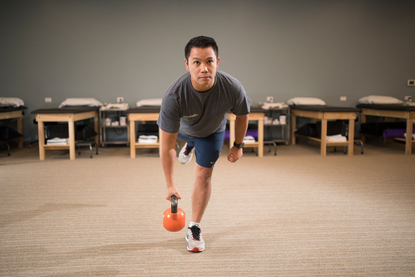 Physical therapy patient using a kettle ball to help strengthen and balance