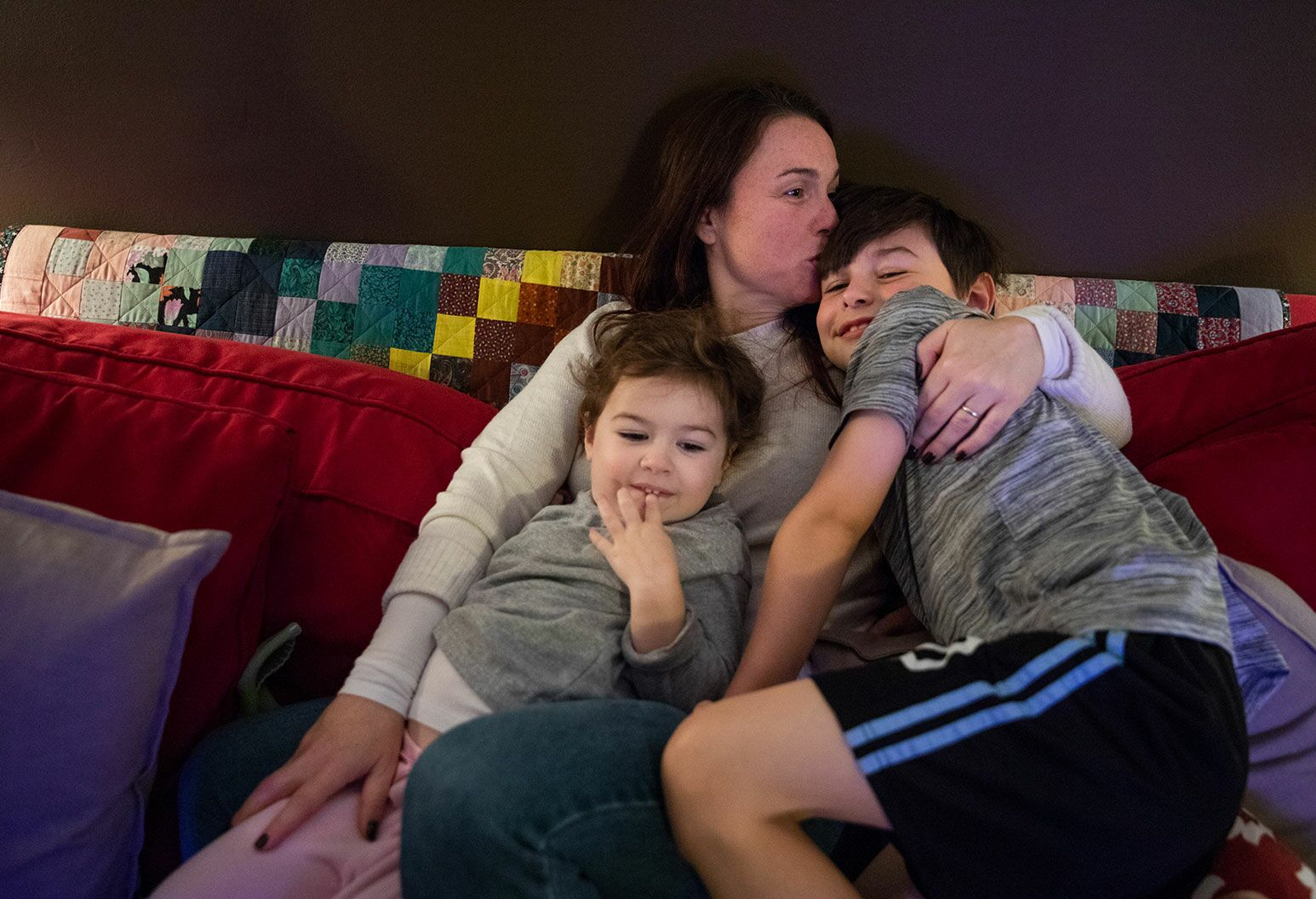 A woman with long auburn hair sits on a couch with a young girl and young teen boy sitting on top of them. She kisses the young teen on the forehead.