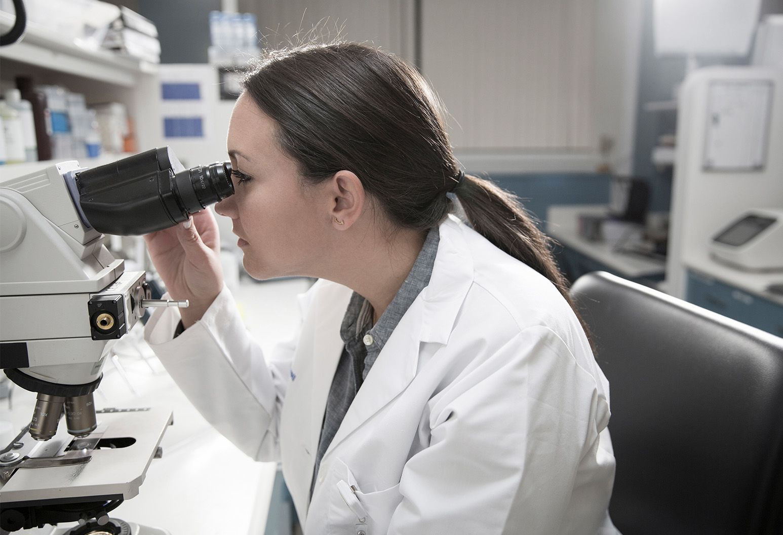 Young woman with brown hair and white lab coat is seen from the side looking into microscope