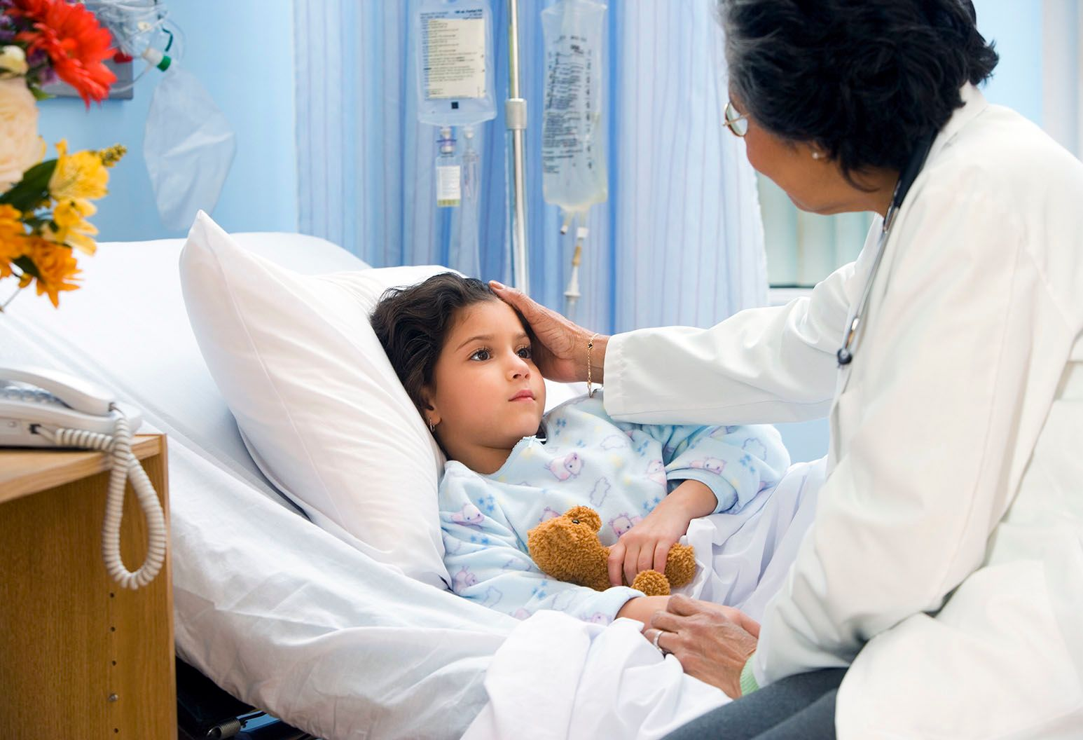 A little girl with brown hair is holding a teddy bear laying in a hospital bed. An older female clinician sits on the bed and has her hand on her head, consoling her