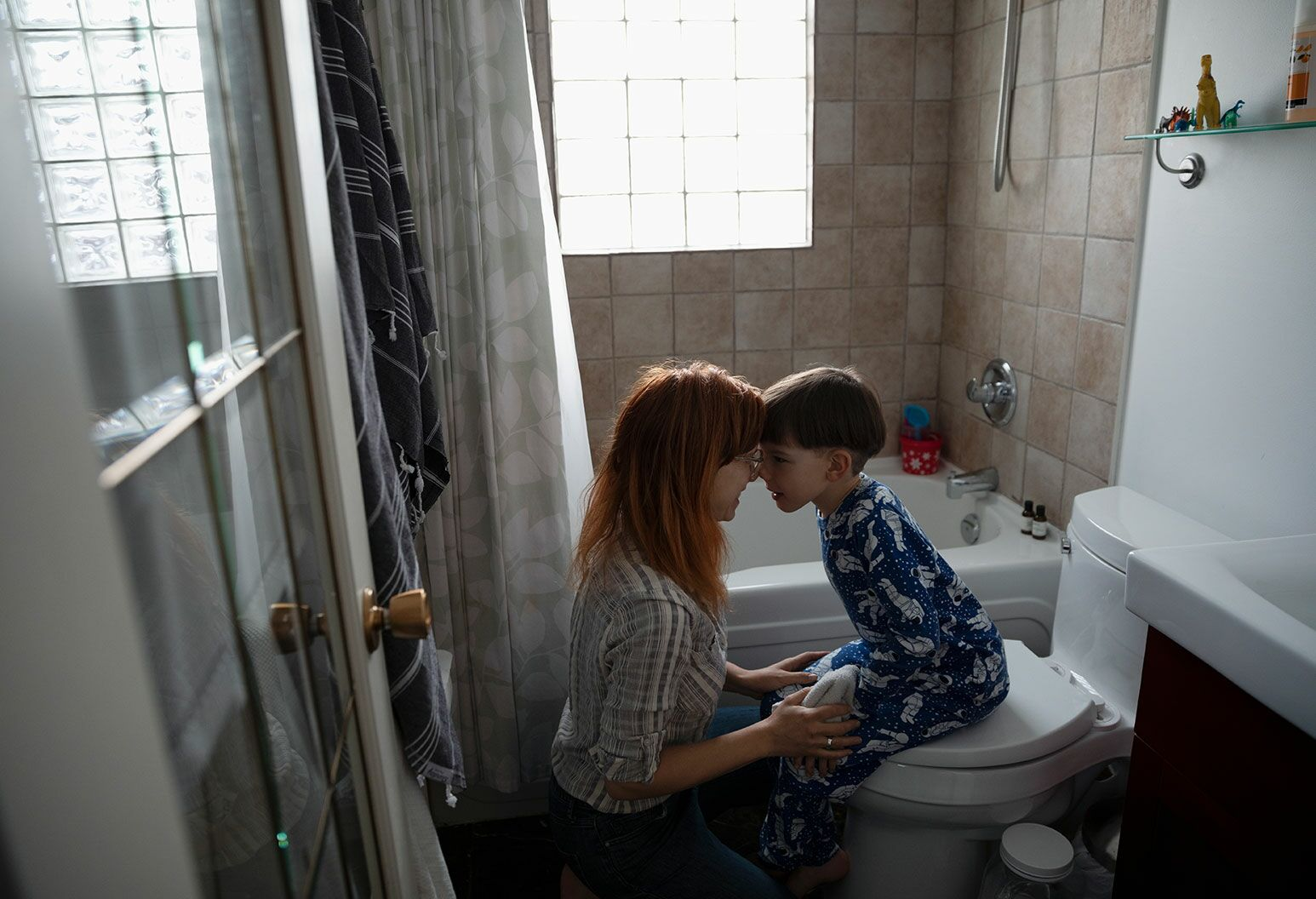 A woman with red hair and glasses kneels in front of a toilet where a young boy in pajamas sits on the lid resting his forehead on hers.