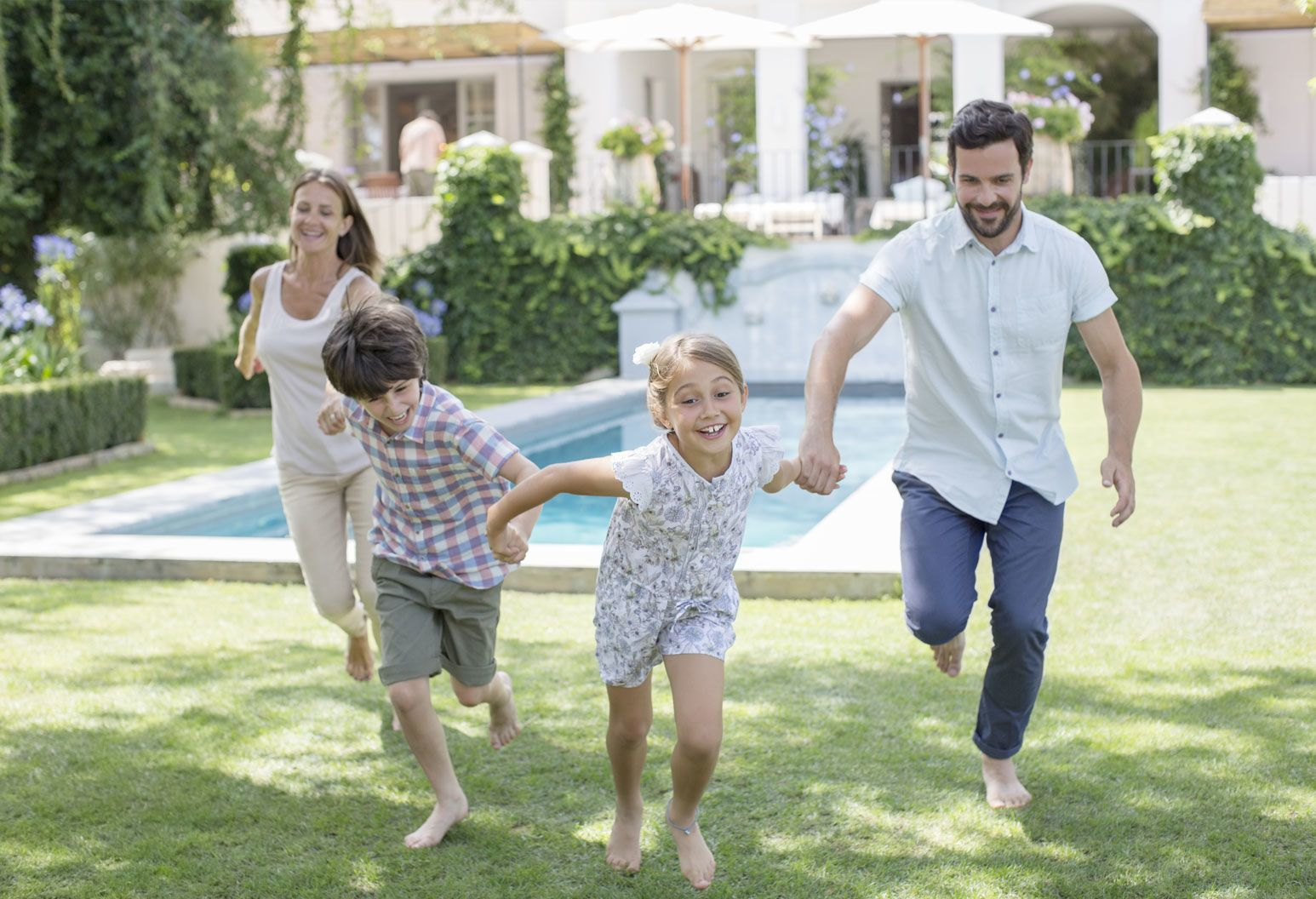 A mom, dad and two young kids hold hands and run together. They are in a backyard with a pool behind them. They're all barefoot and smiling.
