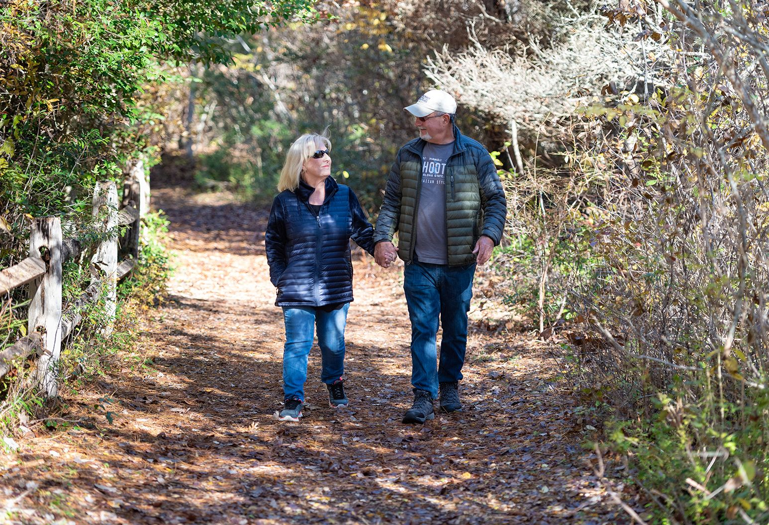A middle-aged couple holds hands and walks down a sun-lit nature trail together.