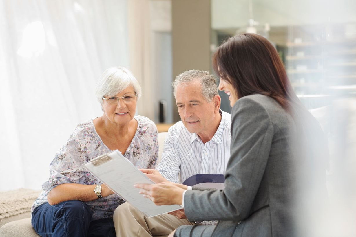 A female goes over a care plan with an elderly couple.