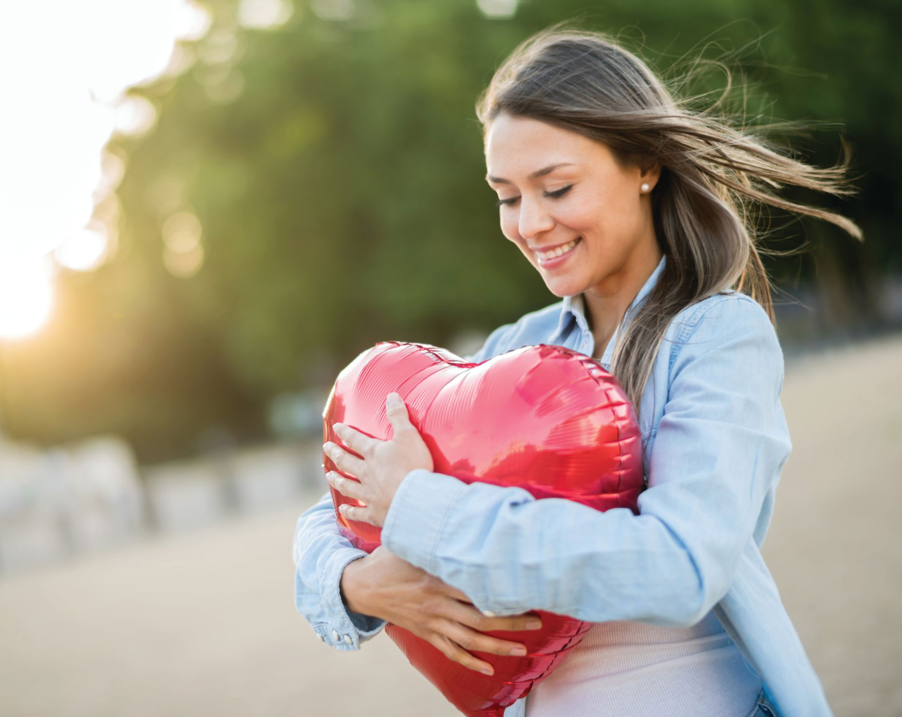 Woman holding a heart image.