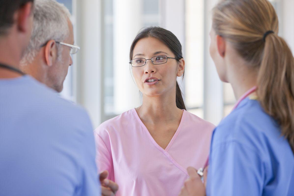 A nurse speaks to other nurses