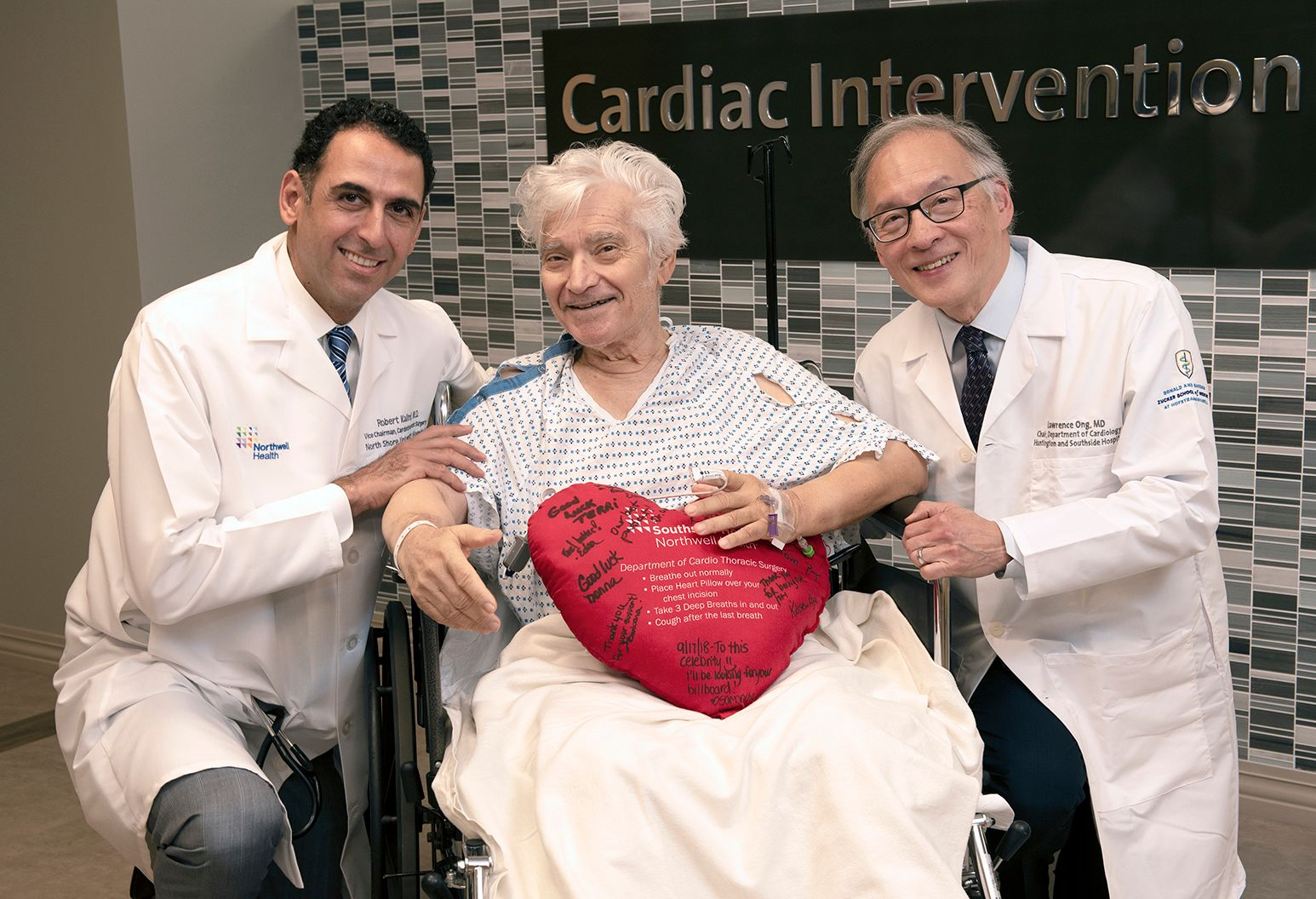 An elderly male patient with white hair wearing a patient gown is sitting in a wheel chair holding a heart pillow. Two doctors wearing Northwell branded white coats kneel beside him and smile.