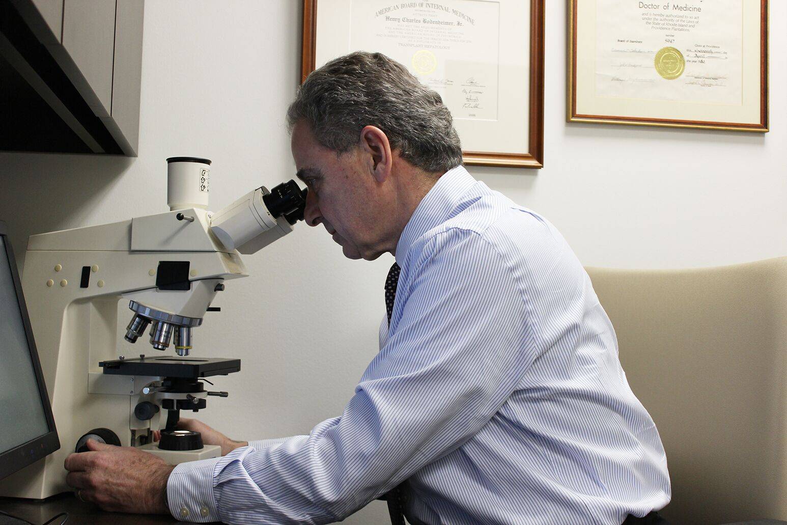 Henry Bodenheimer, MD, looks through a microscope. He is medical director of Northwell's liver transplant program, the first program of its kind on Long Island.