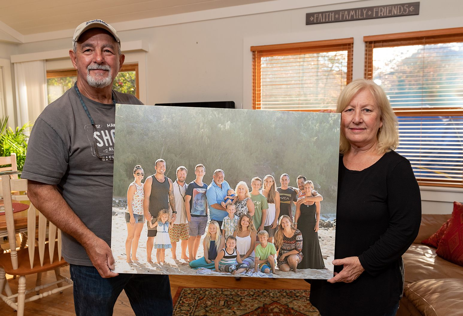 A middle-aged couple stands in living room and holds up a giant photo of their kids and grandkids.