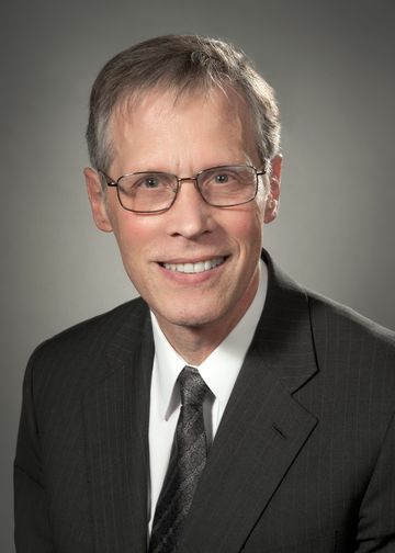 James Crawford, MD, wearing a grey suit and tie