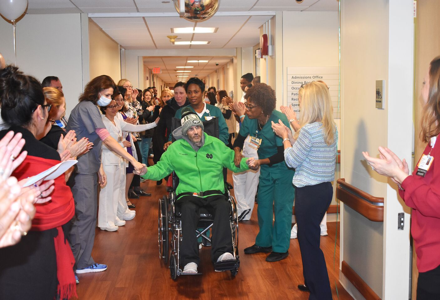 Matthew Malley is pushed in a wheelchair down a hospital hallway, surrounded by staff clapping, cheering, and offering sentiments of support.