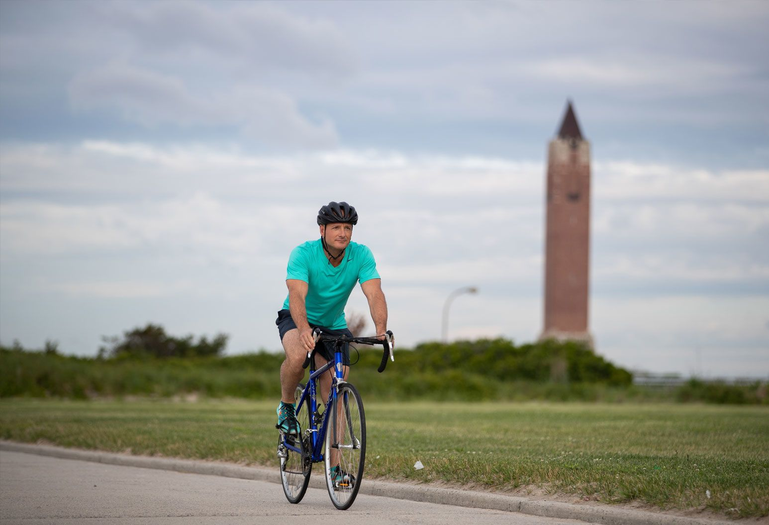 A man wearing a bright blue shirt and black shorts rides a bike on the Jones Beach boardwalk. He's wearing a black helmet.