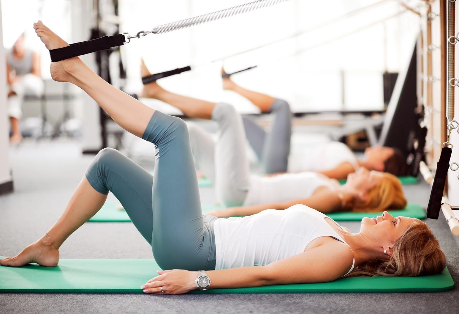 Women lying on the exercising mat and using Pilates machine.