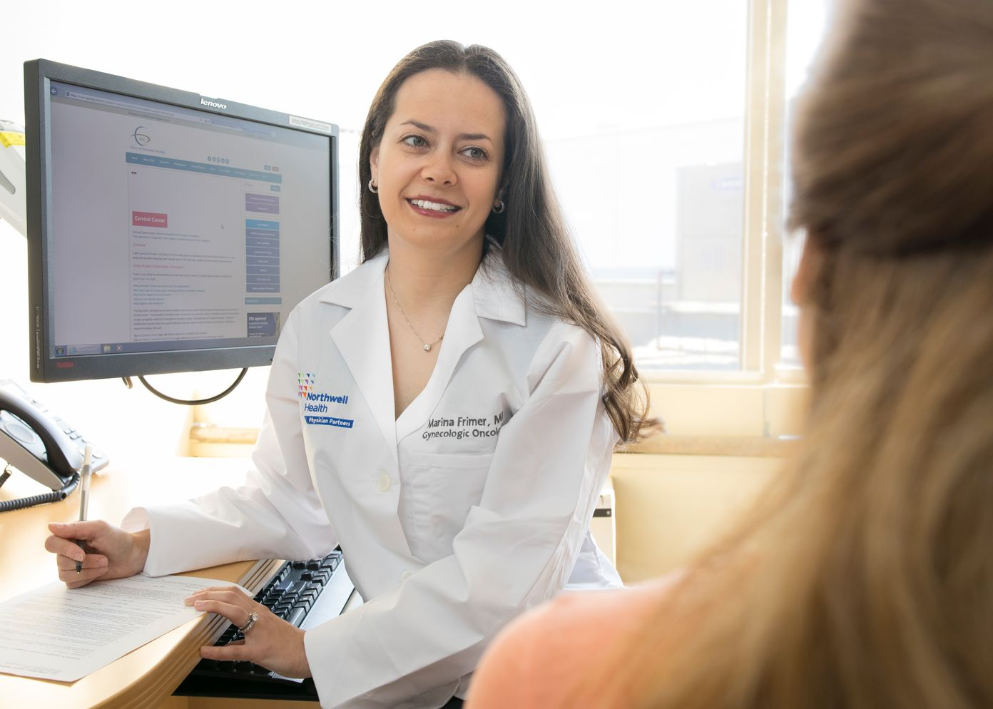 Doctor sitting at desk smiling at patient as she writes something down