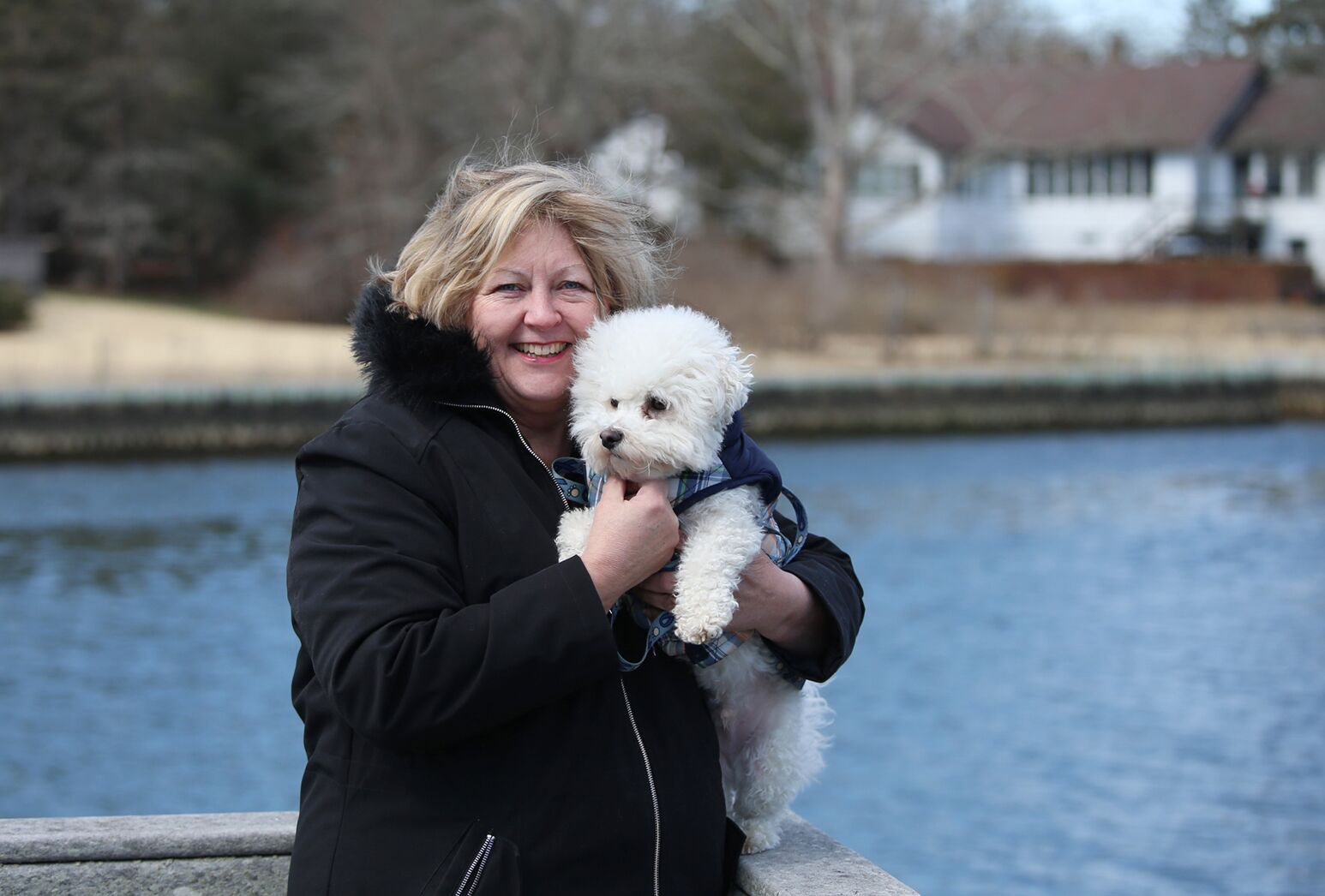Middle-aged, blonde-haired woman standing next to a lake, holding a white dog on a winter day.