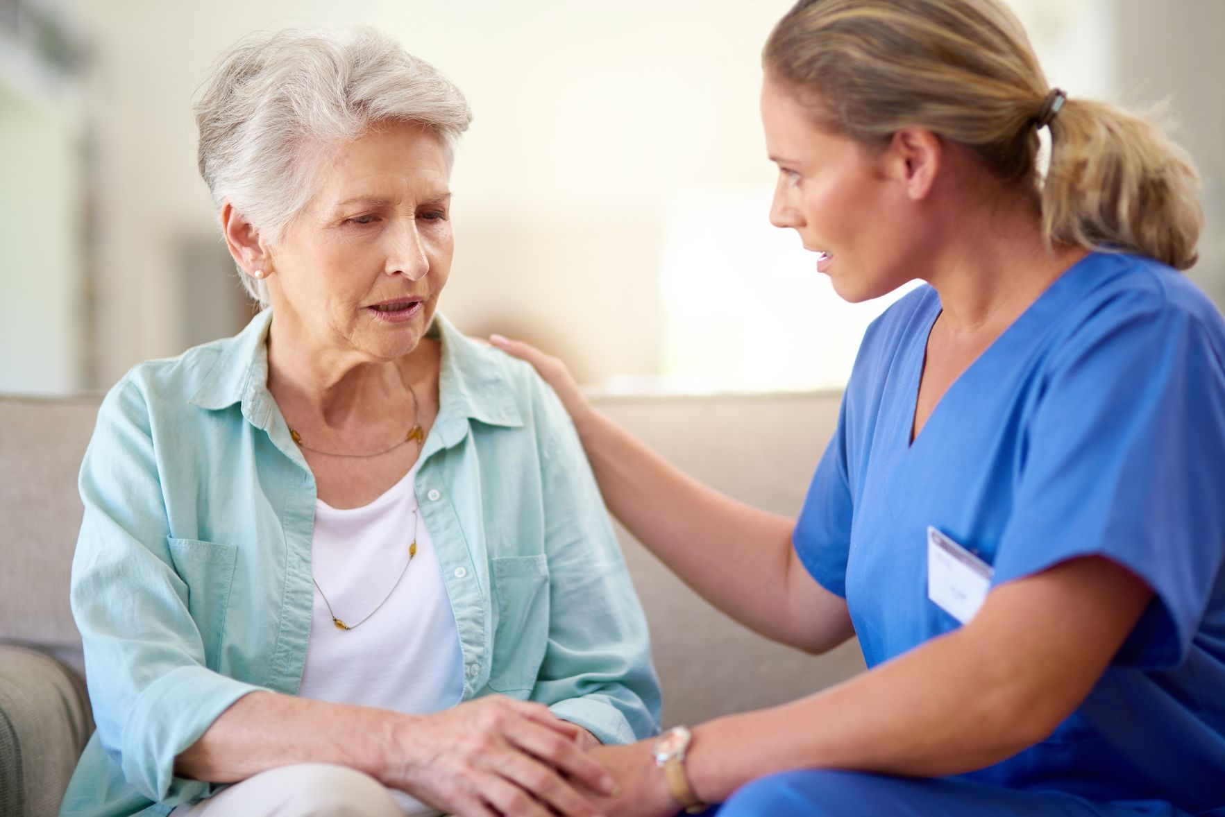 A female clinician speaks to an elderly woman.