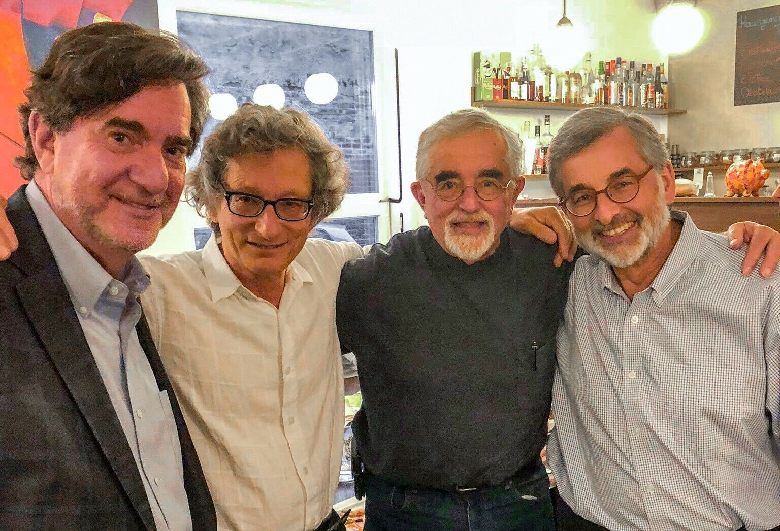 Four men pose for a picture, smiling, with their arms resting on each other's shoulders.