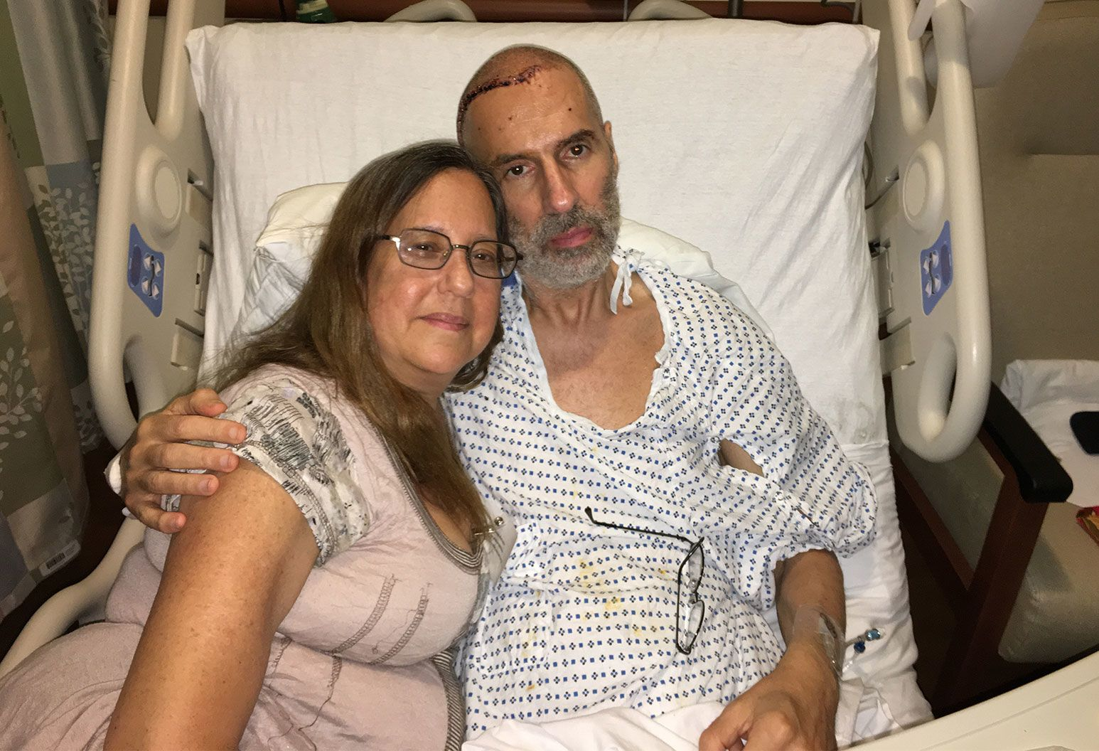 A bearded man sits on a hospital bed next to a woman. He has a shaved head with some red marks along the hair line and a grey beard. A woman sitting next to him smiles as he has his arm around her shoulder.