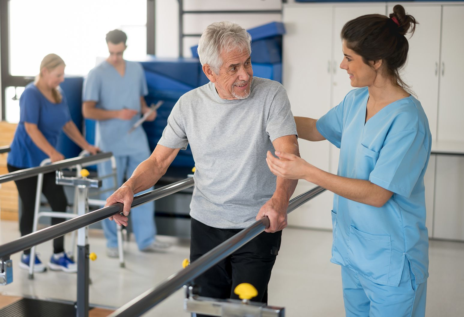 Cheerful senior man using parallel bars to walk and physiotherapist smiling at him very happy while another patient and professional are walking at the background