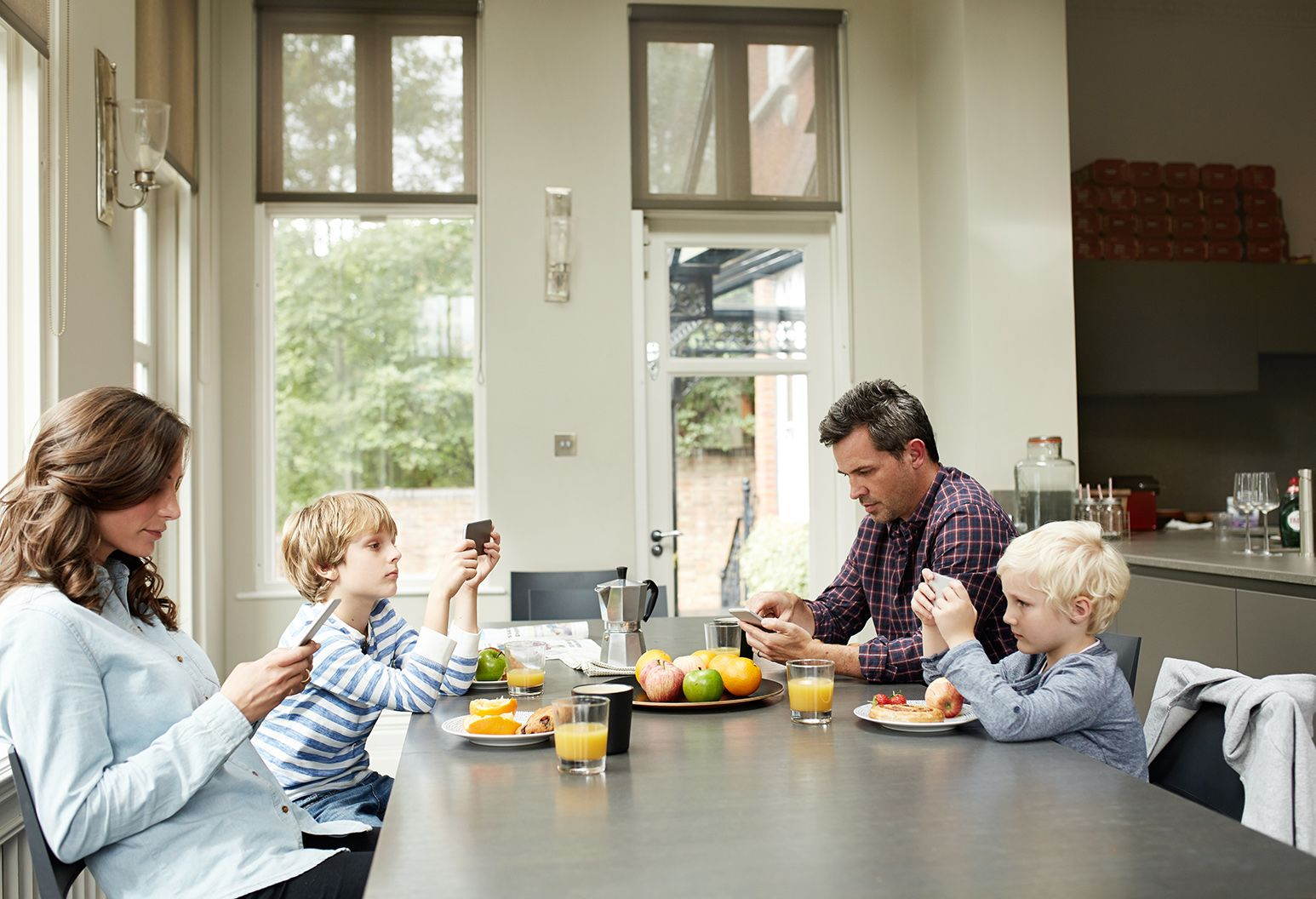 A mother, father and two little boys, ages 6 and 8, sit around a kitchen table. They are all on their cell phones. They each have a plate of food in front of them but they do not eat.