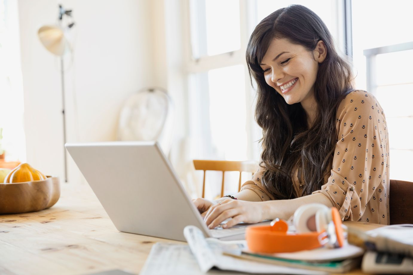 woman sitting at table, smiling and looking at laptop