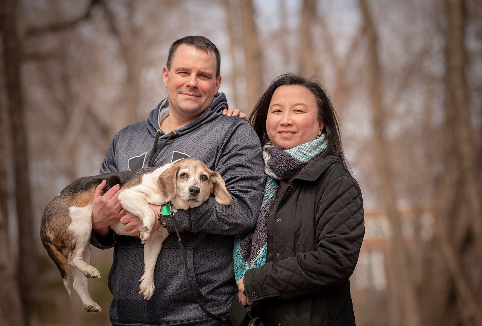 Man and woman standing outside, holding a small dog.