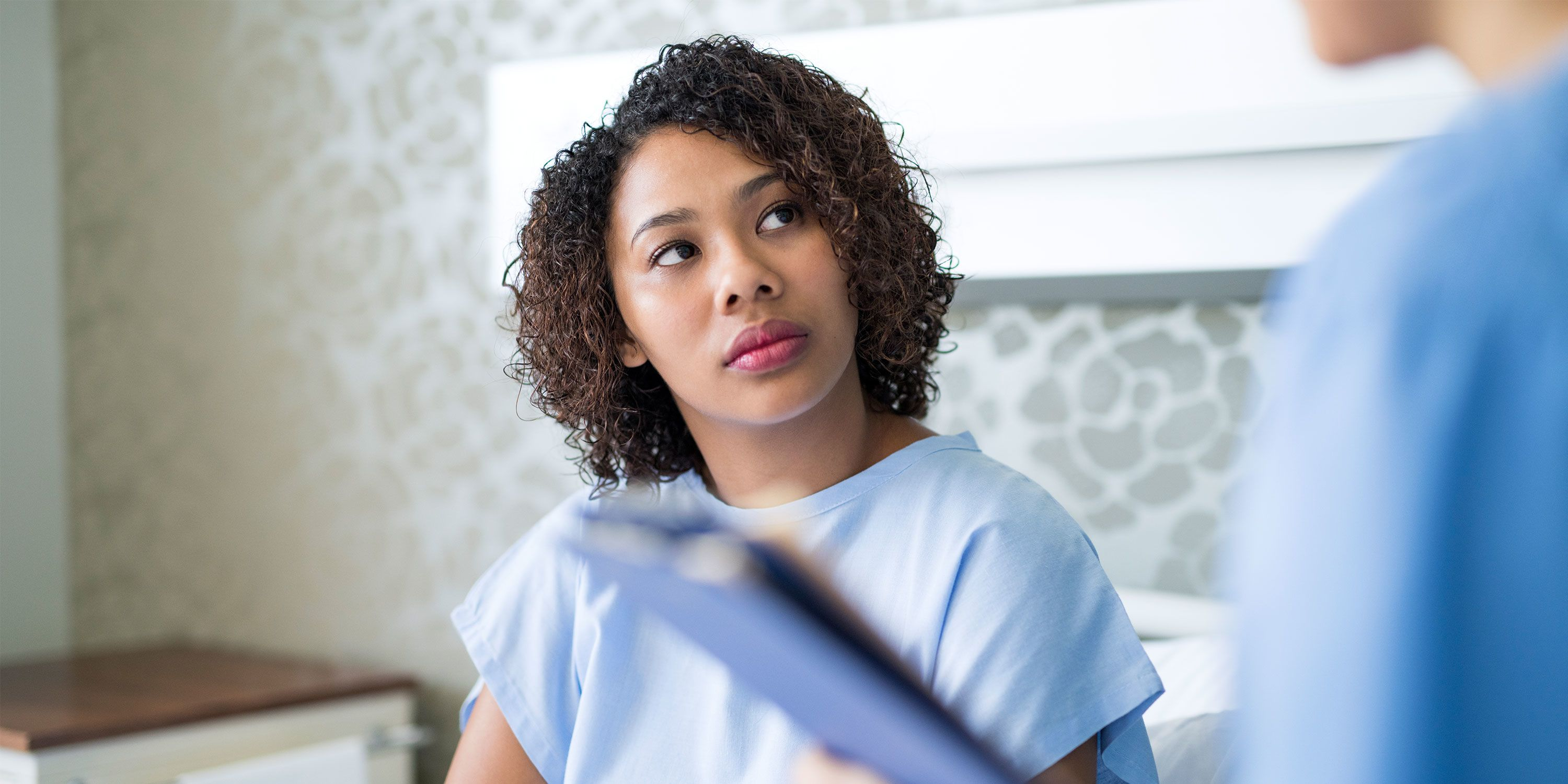 A woman in a patient outfit sits in a hospital room looking up at a doctor that is not fully seen.