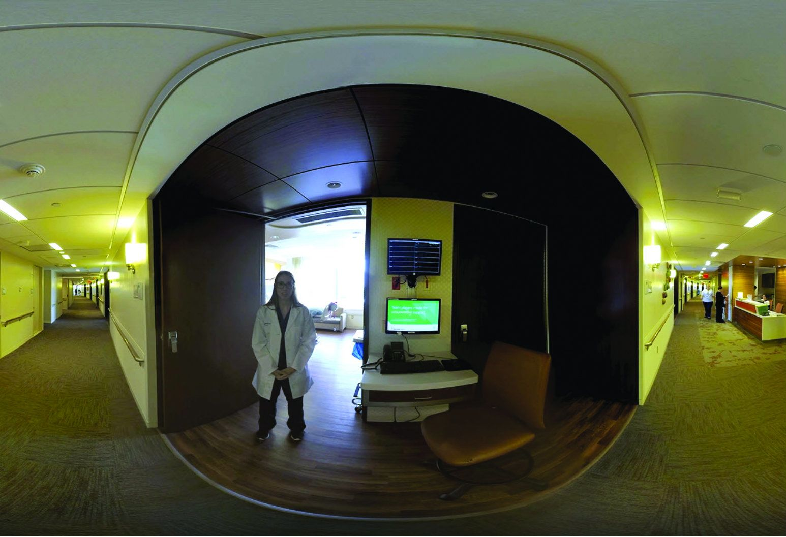 A woman wearing a lab coat over doctor's scrubs stands in front of the open door of a virtual reality training room. Bright light streams out the door. Next to the woman and the door is a desk with a keyboard and an intercom on it, with two monitors attached to the wall it stands against. On the left and right of the room, the rest of the hallway can be seen. It is long and carpeted. Northwell Health's Center for Learning and Innovation has begun including virtual reality simulation training in its education programs to develop medical students' situational awareness.