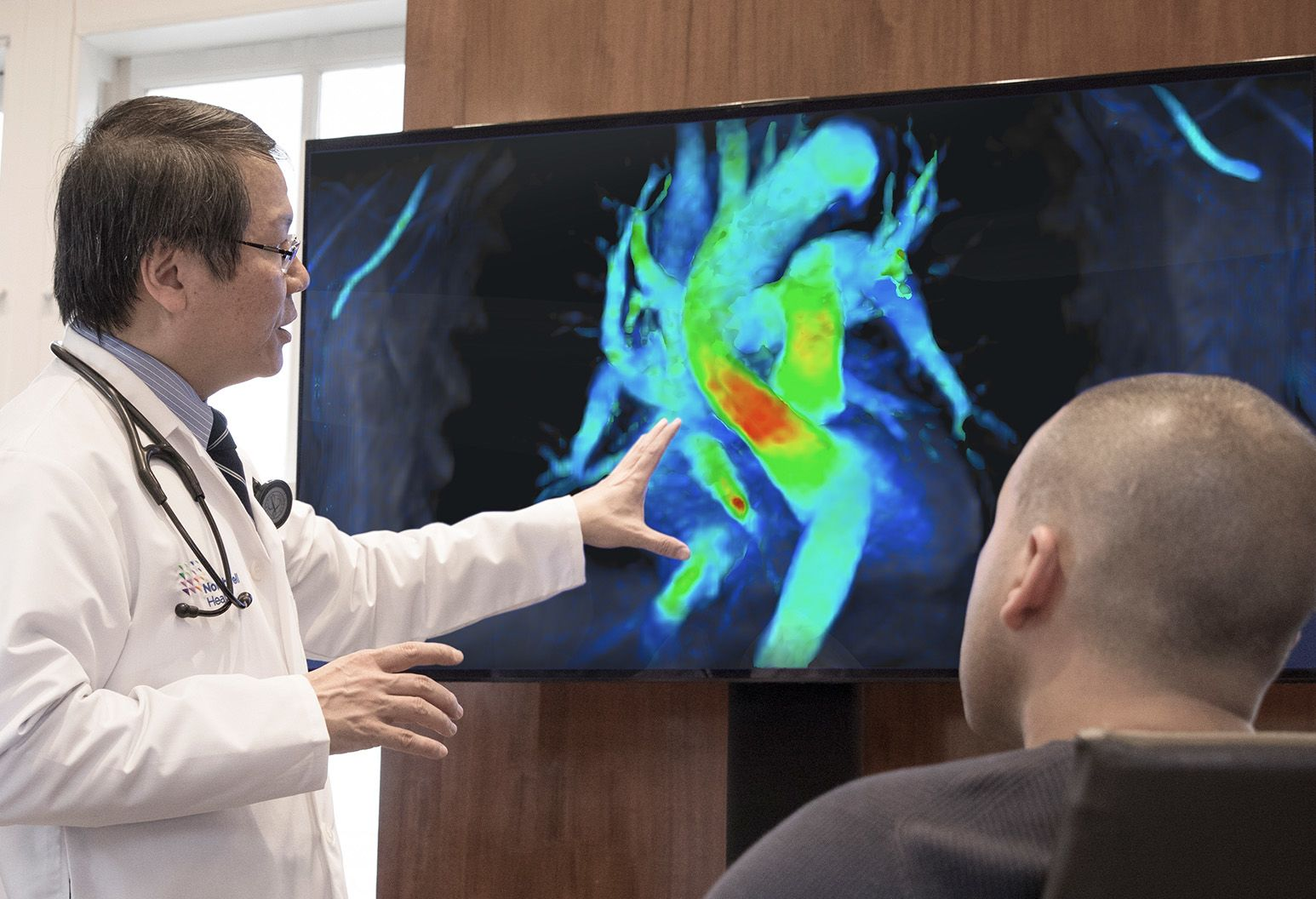 Male doctor in white lab coat points to screen on the wall showing 4D images of the heart to male patient