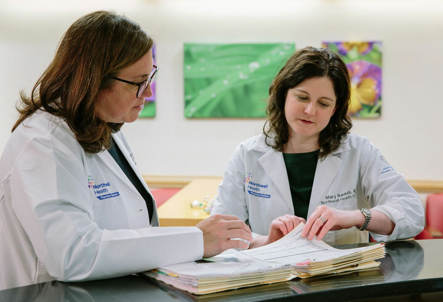 Two women wearing white lab coats look at papers