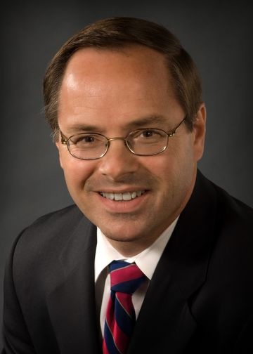 Gerard Brogan, MD, wearing a black suit and red and blue tie