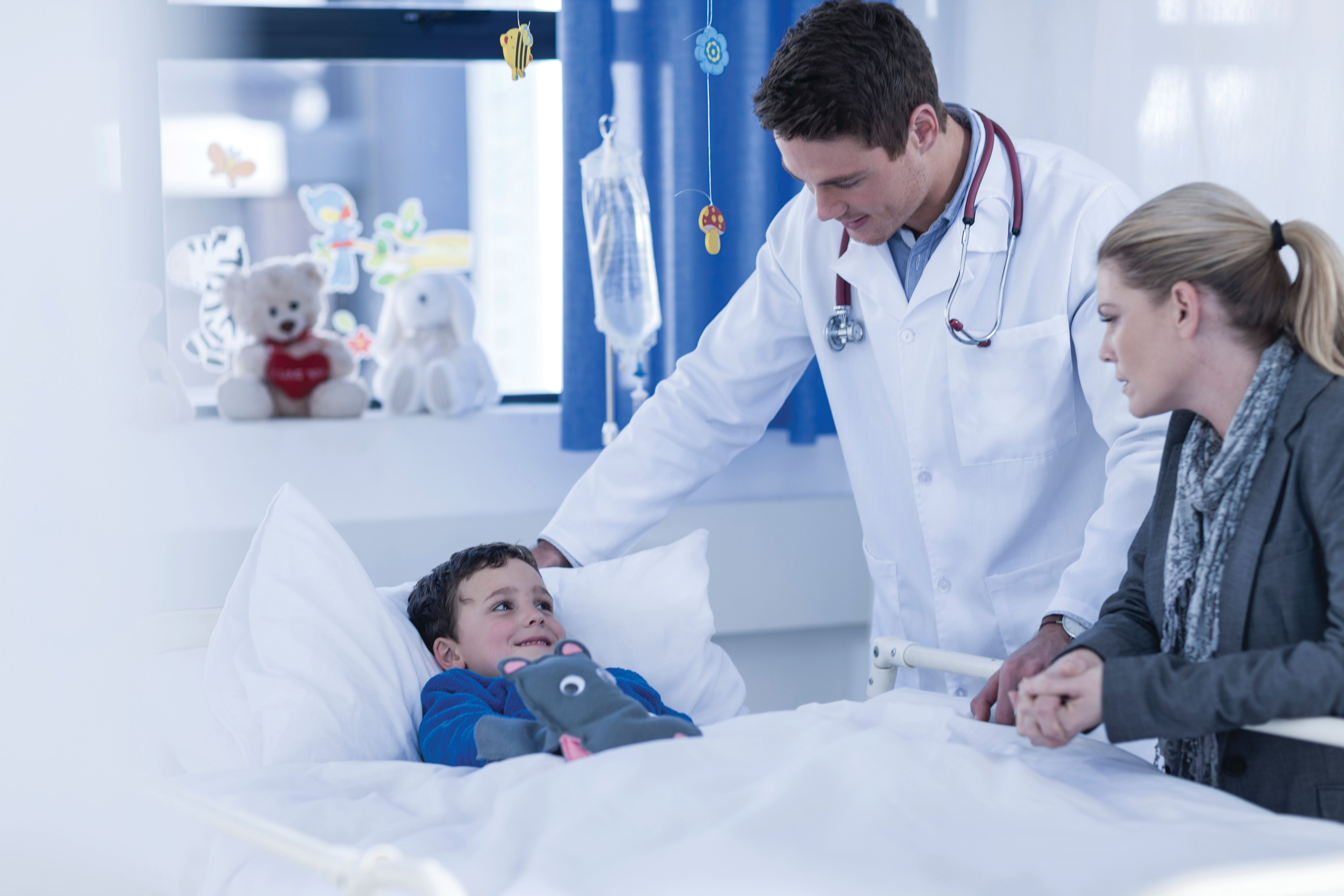A doctor and mother watch over a boy in a hospital bed.
