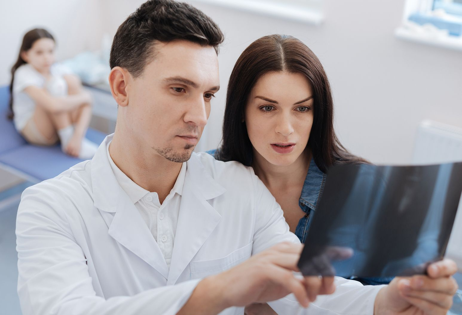 Handsome serious experienced doctor standing near the worried woman and showing her an X ray photo while explaining the problem