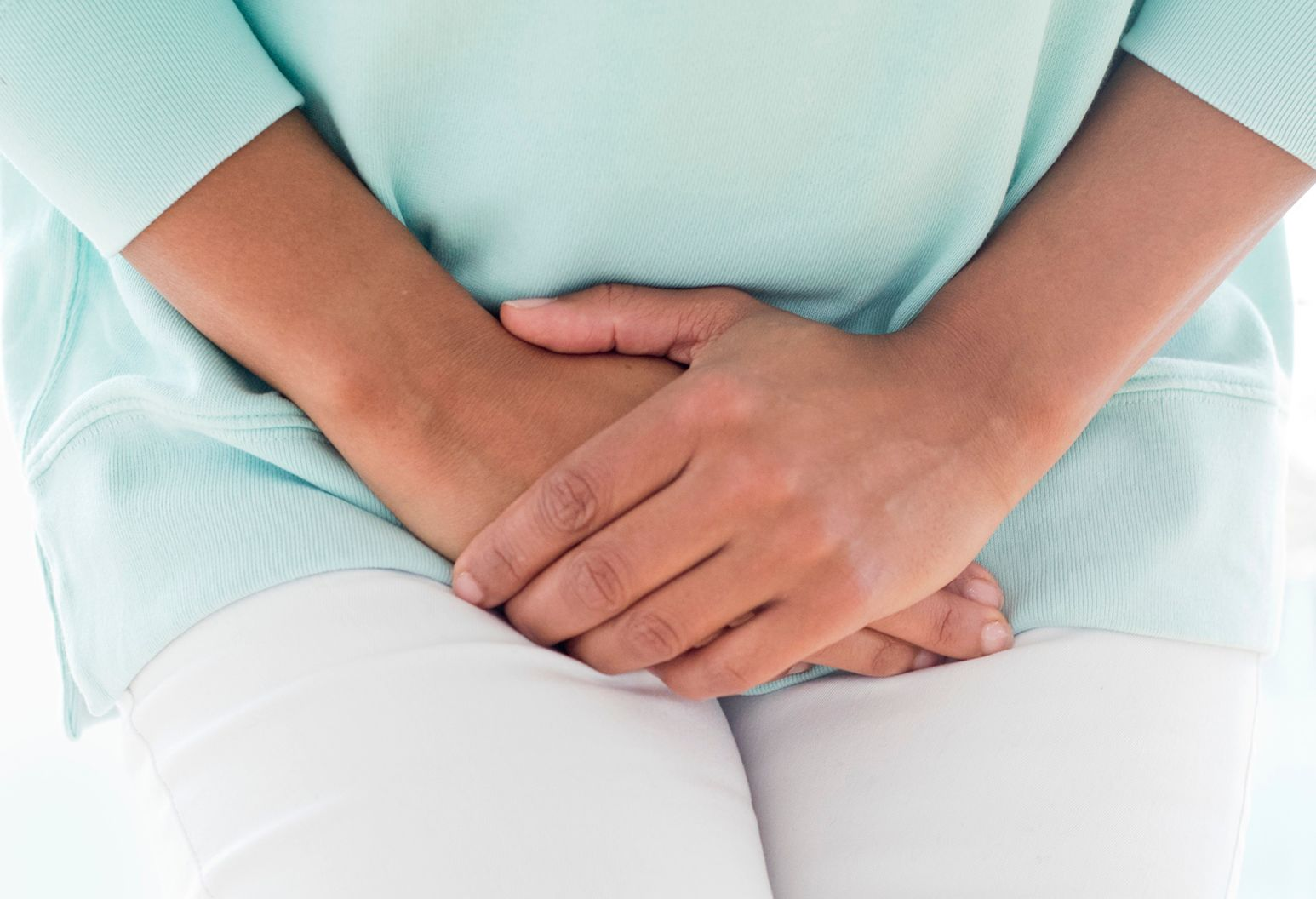 Woman in a blue shirt and white pants clutches her stomach in pain.