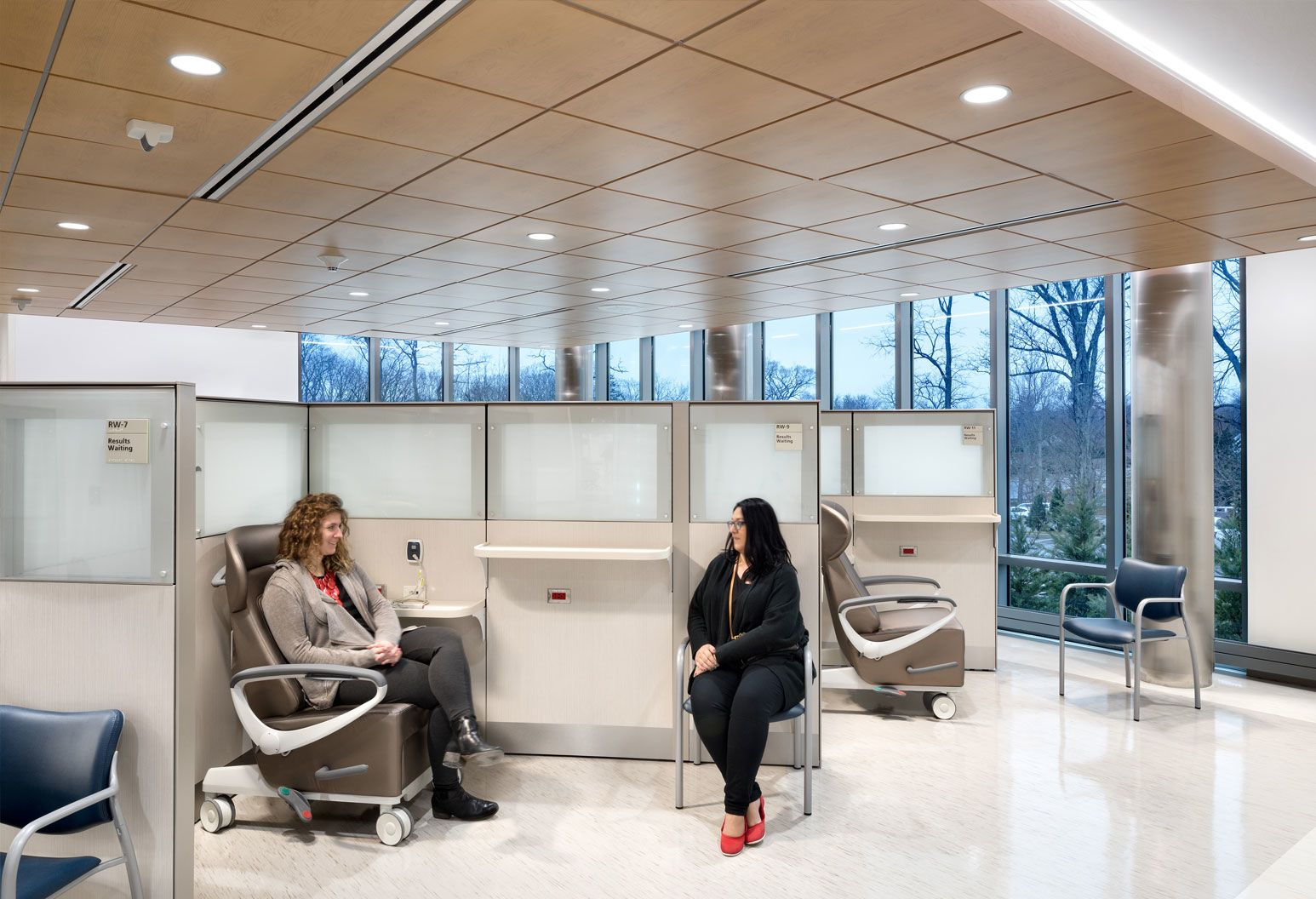 Two women sit in the ED; one is in a chair, and one is in an electric wheelchair.