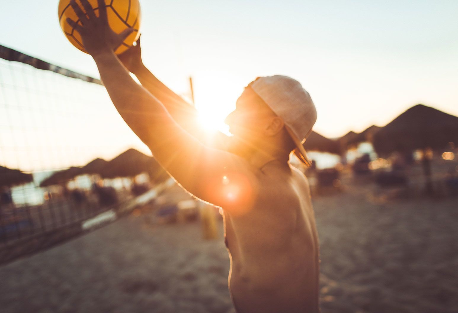 A shirtless man with a cap on backwards is playing beach volleyball as there's a golden sun setting in the background.