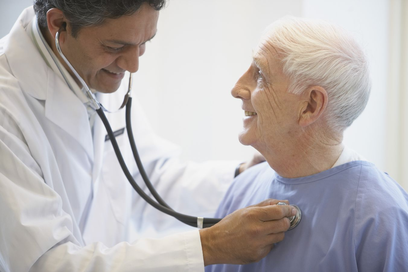 Male doctor with stethoscope is checking heart of smiling older man in blue patient gown.