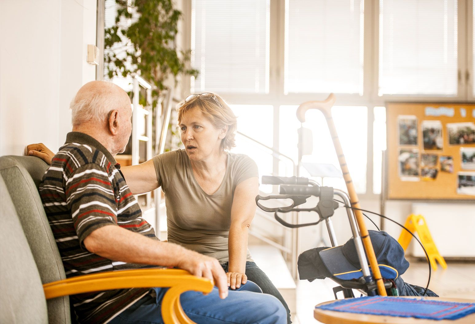 An elderly man sits in a chair next to a middle aged woman. The woman is speaking. They are in a brightly-lit space. There is a cane and walking aid next to them.