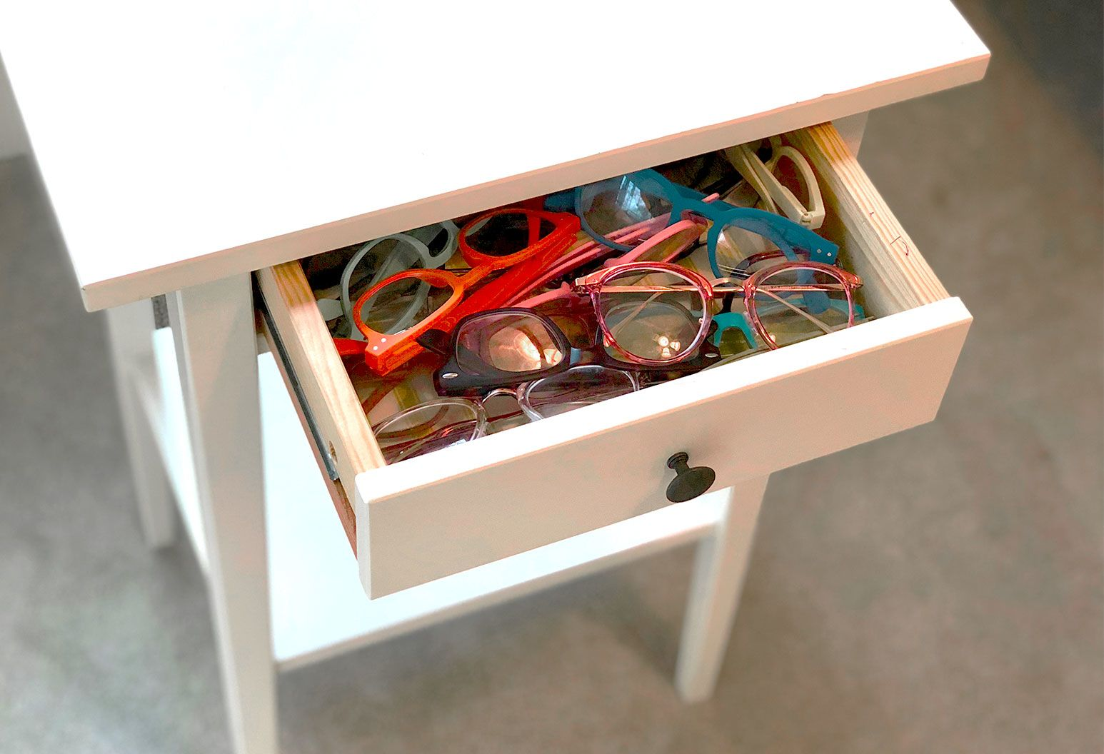 White night stand with the drawer ajar filled with eye glass frames of multiple colors.