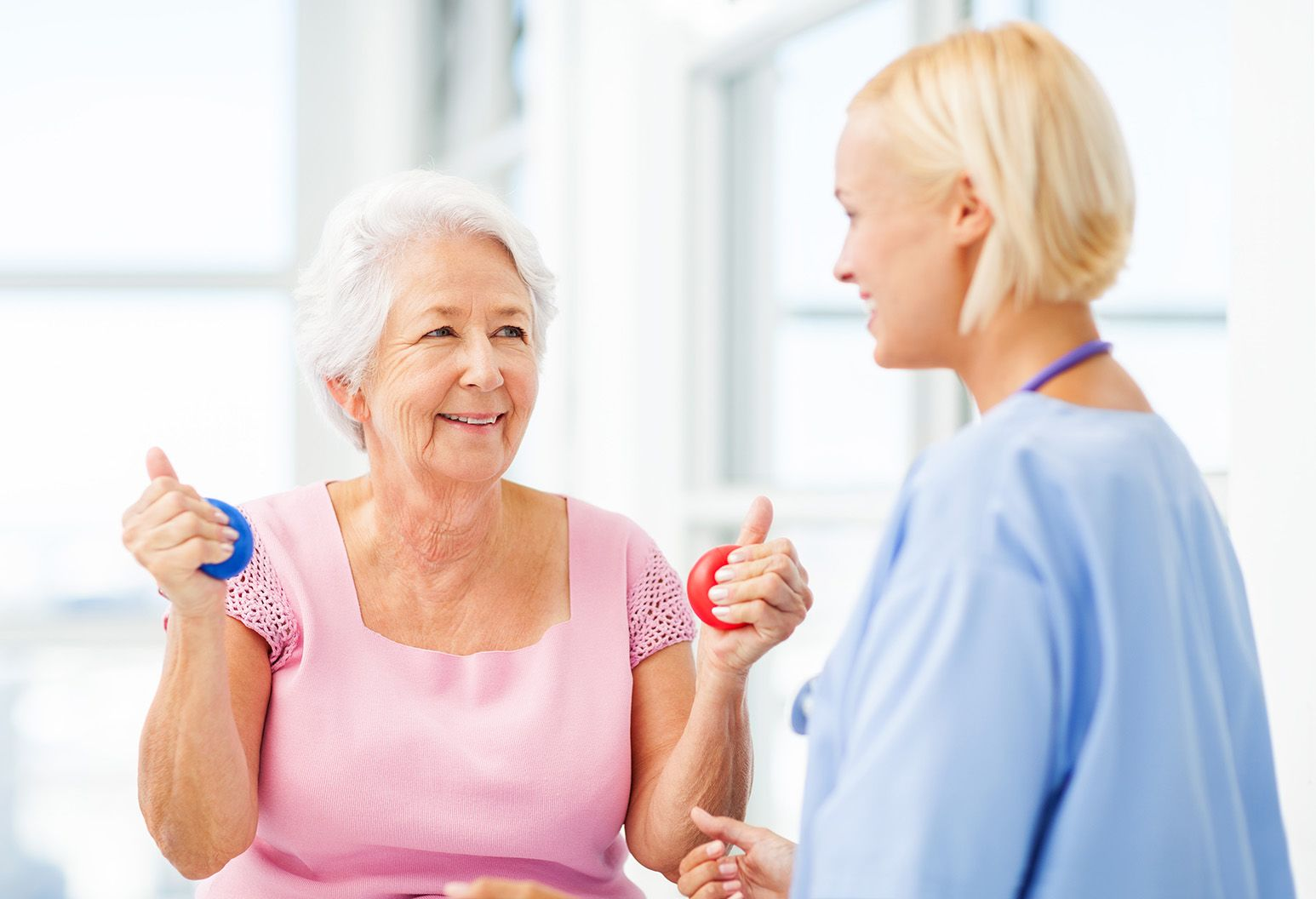Female young nurse assisting senior patient in squeezing hand therapy balls at nursing home