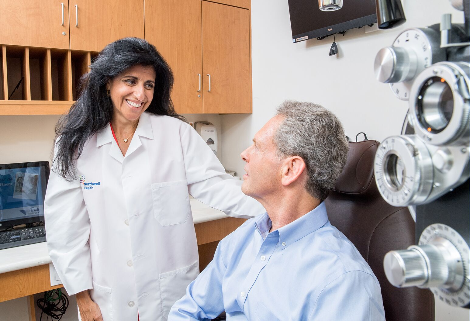 Eye physician smiling at patient who is sitting in exam room chair.