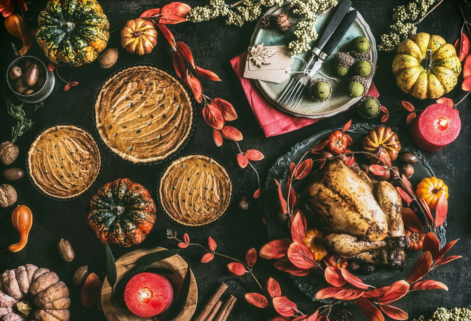 Thanksgiving day dinner table with roasted whole chicken or little turkey , pumpkin pie on dark rustic background with plates, sauce, cutlery, table setting tags, burning candles, red autumn leaves, nuts and festive decoration , top view, still life, flat