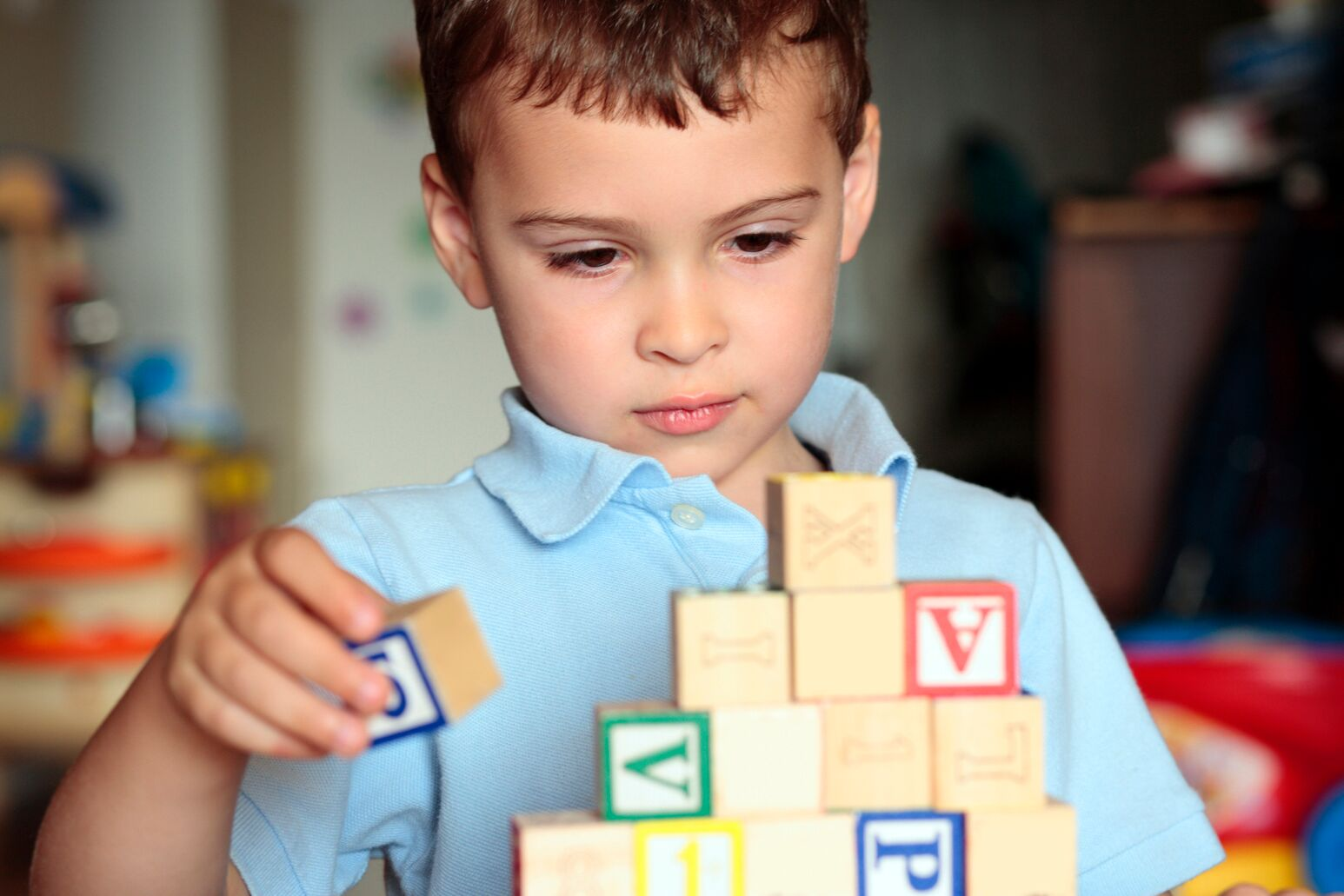 A boy plays with lettered blocks