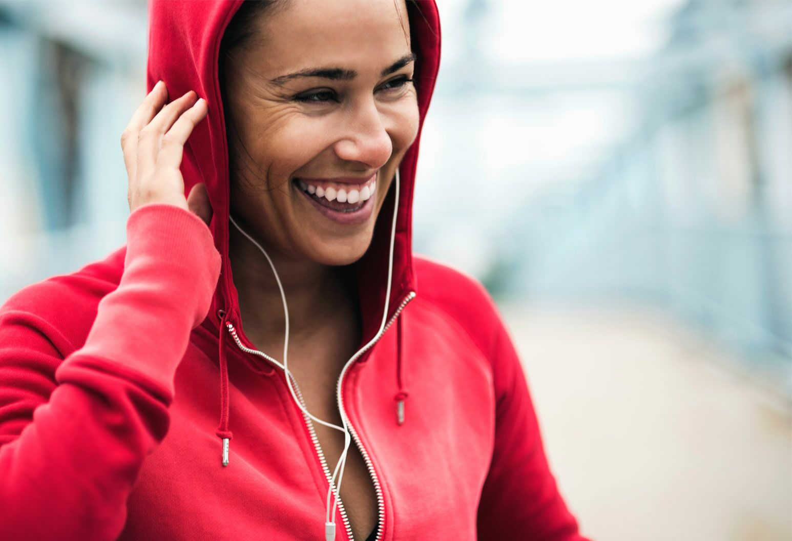 Women in red sweater hoodie enjoying time exercising and listening to music.