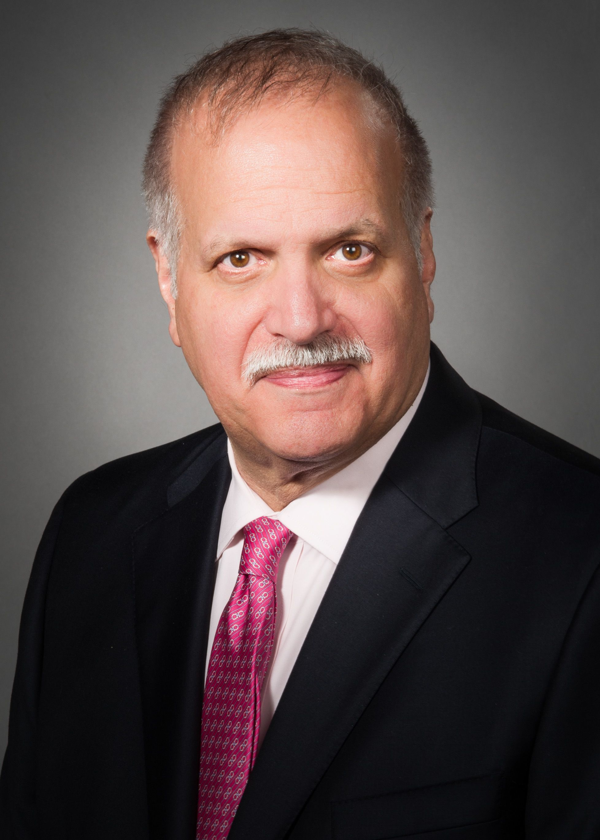 Peter Bruno, MD, wearing a black suit and a red tie