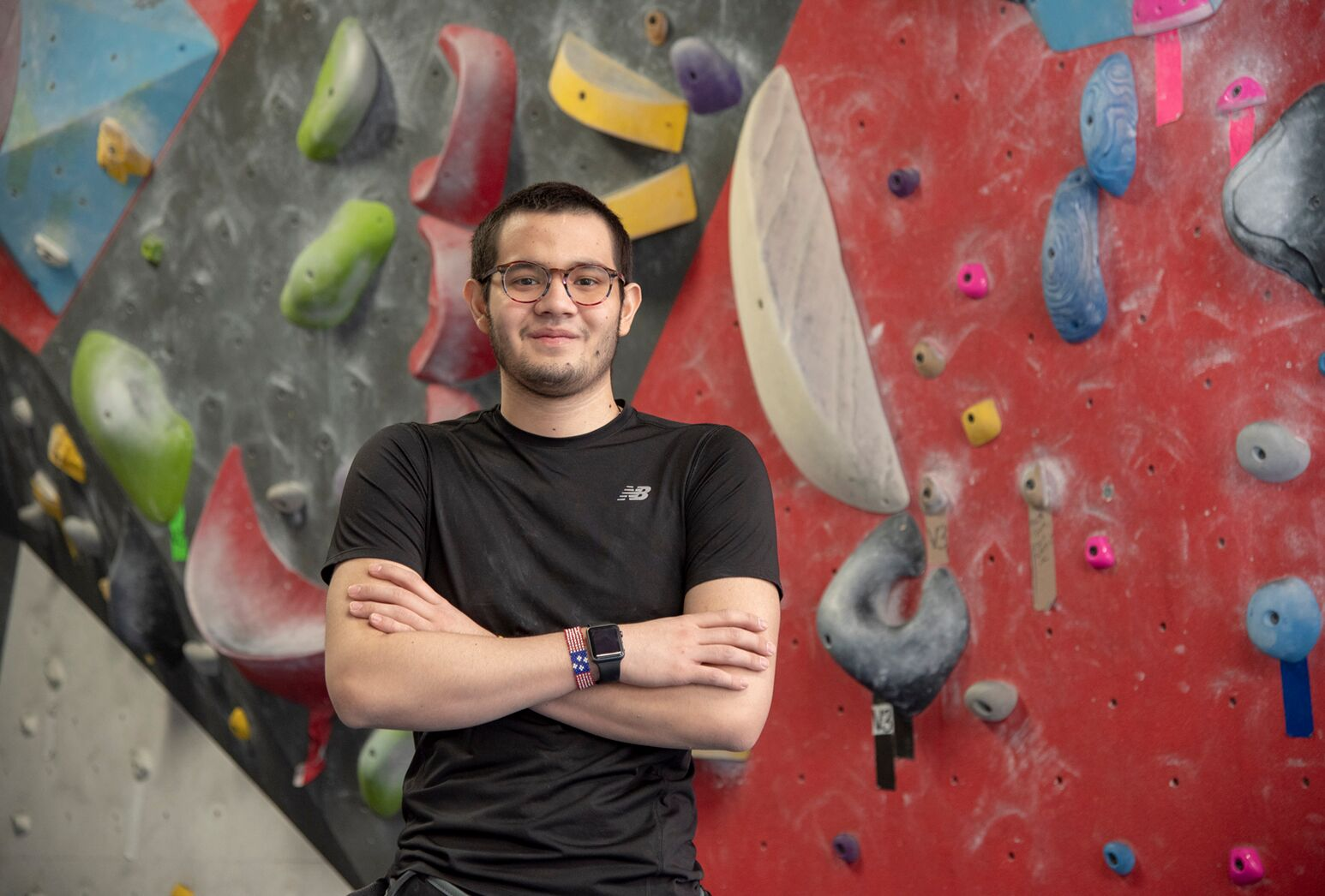 Young man standing in front of colorful climbing wall.
