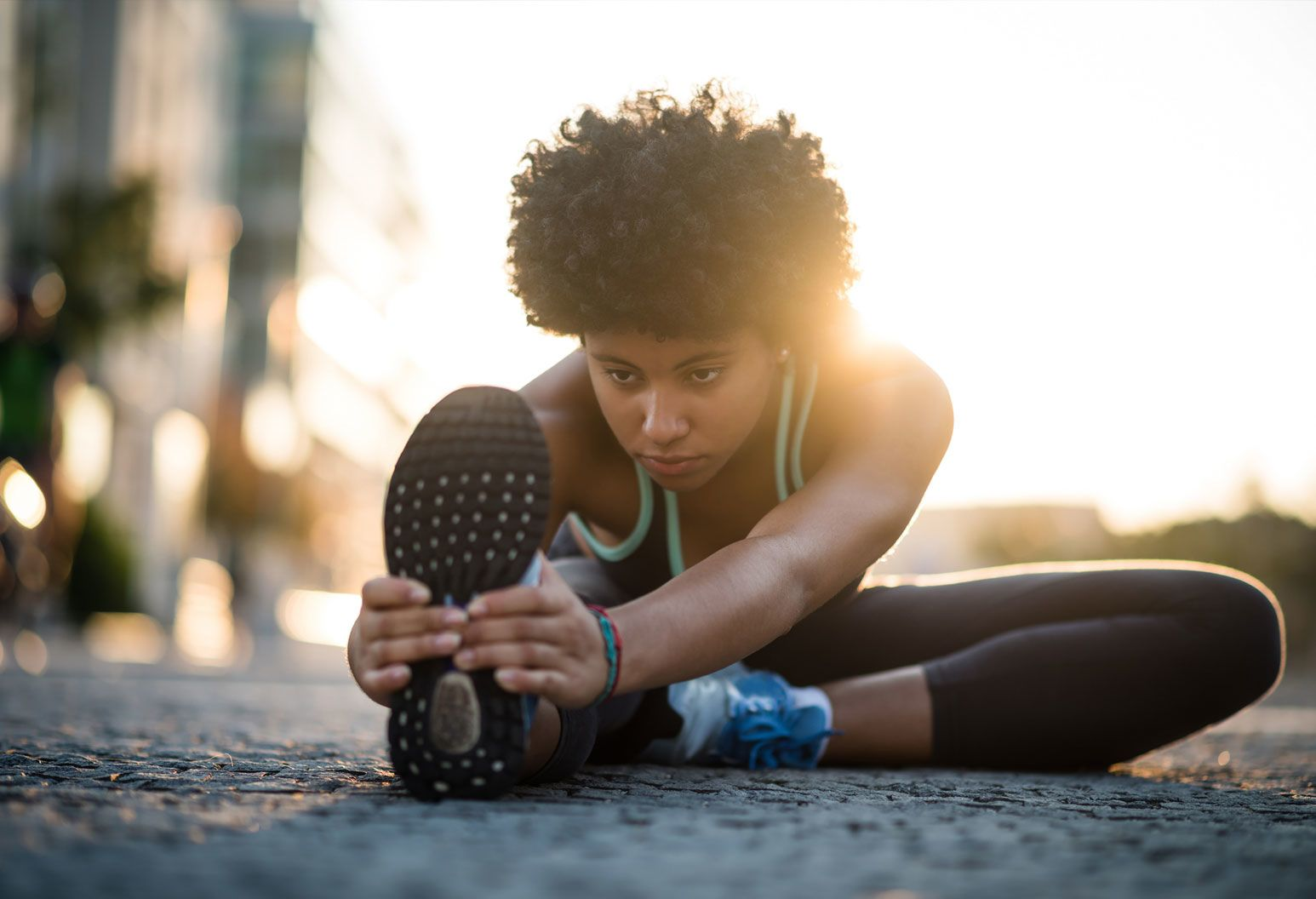 An african american woman with short, curly hair sits on the concrete ground outside and stretches. She has one leg out in front of her and she leans over it. She's wearing black leggings and a black tank top with a bright green trim.